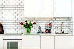 红色和白色郁金香新鲜的花束在厨房用桌上的 家庭内部,设计细节  Minimalistic概念 花 免版税库存照片
