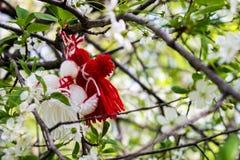 红色和白色颜色两个布洋娃娃,垂悬在白花中是与绿色叶子的樱桃 免版税库存图片