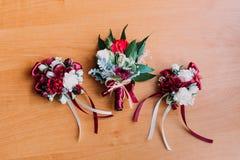 红色和白花三朵美丽的钮扣眼上插的花在木土气背景的 免版税图库摄影
