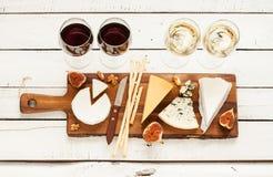 红色和白葡萄酒加上不同的种类乳酪(cheeseboard) 免版税图库摄影