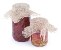 红色和绿色辣椒各式各样的蕃茄和片断与油的在有在白色b在上面隔绝的麻袋布盖子的玻璃银行中 库存图片