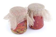 红色和绿色辣椒片断与油和辣味番茄酱的在有在白色backgro在上面隔绝的麻袋布盖子的玻璃银行中 免版税库存照片