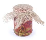红色和绿色辣椒片断与油的在有在白色背景在上面隔绝的麻袋布盖子的玻璃银行中 库存照片
