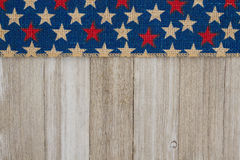 红色和蓝星在被风化的木背景的粗麻布丝带 免版税库存图片