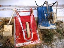 红色和蓝色一轮子推车和铁锹在建造场所附近 库存照片