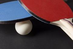红色和蓝色乒乓球桨-在黑色的特写镜头 库存图片