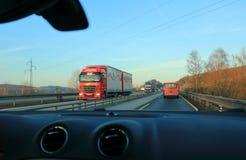 红色和蓝色卡车在欧洲高速公路D1驾驶在日落或日出 免版税库存图片