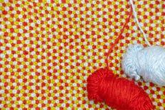 红色和蓝色毛线缠结在被编织的布料背景的与红色,蓝色和绿色羊毛的 图库摄影