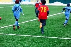 红色和蓝色运动服的男孩踢在绿草领域的足球 青年橄榄球赛 儿童体育竞赛,孩子使用 免版税库存图片