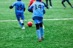 红色和蓝色运动服的男孩踢在绿草领域的足球 青年橄榄球赛 儿童体育竞赛,孩子使用 免版税图库摄影