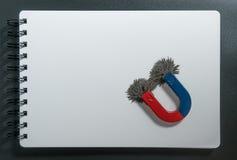 红色和蓝色马掌磁性的磁铁或有铁粉末磁场的物理和指南针在白皮书笔记本背景 免版税库存图片