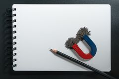 红色和蓝色马掌磁性的磁铁或的物理,铅笔和指南针有铁的搽粉磁场在白皮书笔记本后面 库存照片