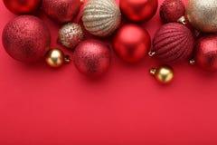 红色和金子圣诞节球在红色背景 免版税库存照片