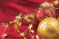 红色和金子圣诞节电灯泡在红色背景 库存照片