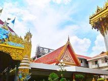 红色和金寺庙屋顶有一朵象天空的背景和白色云彩在白天 库存照片