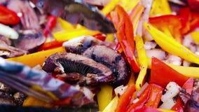 红色和黄色喇叭花胡椒烤用葱、蘑菇和调味料在热的木炭 股票录像