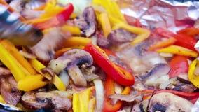 红色和黄色喇叭花胡椒被转动与钳子和烤与葱、蘑菇和调味料在热的木炭 股票视频