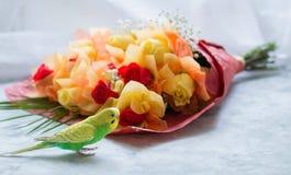 红色和黄色玫瑰年轻波浪鹦鹉和花束白色表面上的 免版税图库摄影