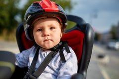 红色和黑盔甲位子自行车的小女孩在城市公园 库存照片