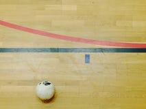 红色和黑线标记和在硬木体育地板上的橄榄球balll 用完难倒 免版税库存照片