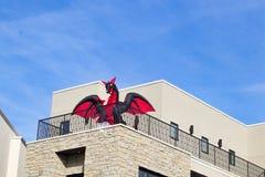 红色和黑色炸毁在企业大厦阳台的龙反对蓝天为万圣夜 免版税图库摄影