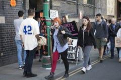 红色和黑牛仔裤的一个姜女孩在Bricklane走 免版税库存图片
