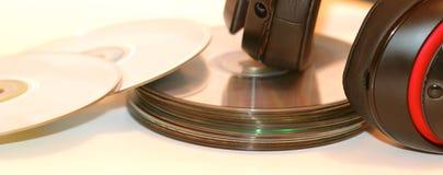 红色和黑立体声耳机和紧凑音乐圆盘 免版税图库摄影