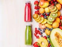 红色和绿色圆滑的人和汁液饮料在瓶用各种各样的新鲜的有机果子和莓果成份在白色木 免版税图库摄影