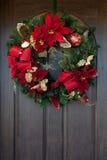 在一个木门的一个红色圣诞节花圈 图库摄影