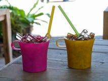 红色和黄色塑料杯子可乐或焦炭与冰在木tabl 图库摄影