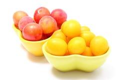 红色和黄色布拉斯李树堆在碗的 奶油被装载的饼干 图库摄影