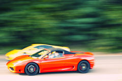 红色和黄色快速地驾车在乡下公路 免版税库存图片