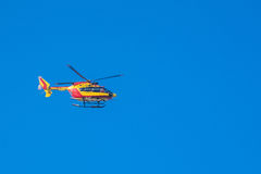 红色和黄色抢救移动与迷离PR的蓝天的直升机 免版税库存图片