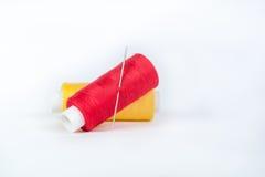 红色和黄色穿线与在白色背景的一根针 库存照片