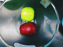 红色和绿色苹果在一个玻璃碗在 免版税库存照片