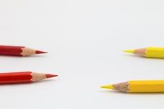红色和黄色蜡笔,在黄色蜡笔的焦点 免版税库存照片