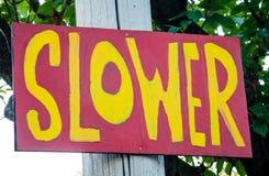 红色和黄色被绘的标志在更慢邻里的街道上 免版税库存照片