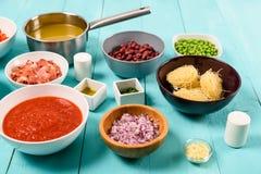 红色和黄色辣椒的果实、葱、烟肉,菜汤、番茄酱、豆和豌豆和细面条面团食品成分 库存图片