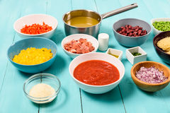 红色和黄色辣椒的果实、葱、烟肉,菜汤、番茄酱、豆和豌豆和细面条面团食品成分 免版税库存图片