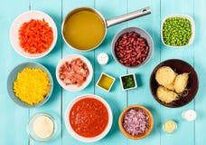 红色和黄色辣椒的果实、葱、烟肉,菜汤、番茄酱、豆和豌豆和细面条面团食品成分 库存照片