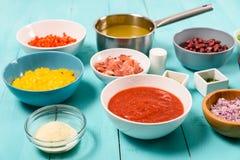 红色和黄色辣椒的果实、葱、烟肉,菜汤、番茄酱、豆和豌豆和细面条面团食品成分 免版税图库摄影