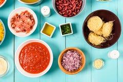红色和黄色辣椒的果实、葱、烟肉,菜汤、番茄酱、豆和豌豆和细面条面团食品成分 免版税库存照片