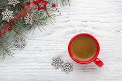 红色咖啡和冷杉分支与在老木破旧的背景的圣诞节装饰 免版税库存照片