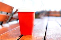 红色咖啡在木桌上的在室外公园 库存图片