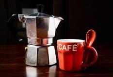 红色咖啡杯和葡萄酒咖啡壶在黑暗的木桌上 图库摄影