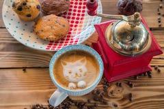 红色咖啡碾、杯子拿铁与一只被绘的猫在牛奶泡沫和饼干在一张老木桌上 图库摄影