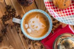红色咖啡碾、杯子拿铁与一只被绘的猫在牛奶泡沫和饼干在一张老木桌上 库存图片