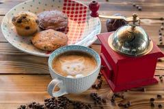 红色咖啡碾、杯子拿铁与一只被绘的猫在牛奶泡沫和饼干在一张老木桌上 免版税库存图片