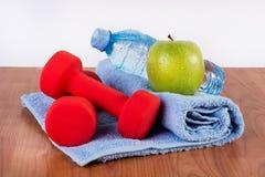 红色哑铃、淡水壶有露水的和绿色苹果在蓝色毛巾在木地板上 图库摄影