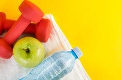 红色哑铃、绿色苹果和淡水壶顶视图有露水的在白色毛巾和黄色空间 免版税库存照片